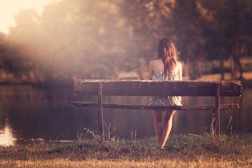 En intelligent kvinde nyder tid alene på en bænk ved en sø