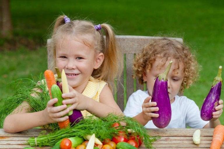 Børn sidder med grøntsager, som er superfoods