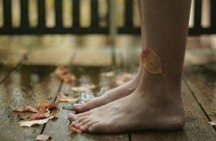 Bare fødder på trægulv med visne blade
