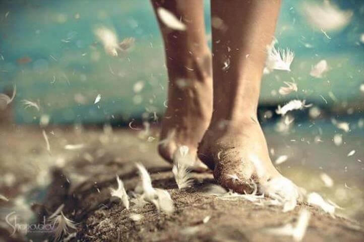 Person går med bare fødder på vej med flyvende fjer