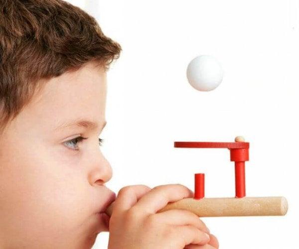 Barn blæser luft ud, så en bold svæver