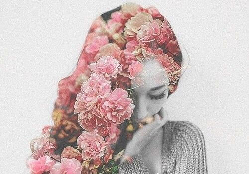 Kvinde med lyserøde blomster i håret viser, hvordan sanser påvirker følelser, da hun bliver berørt at blomsternes duft og farve