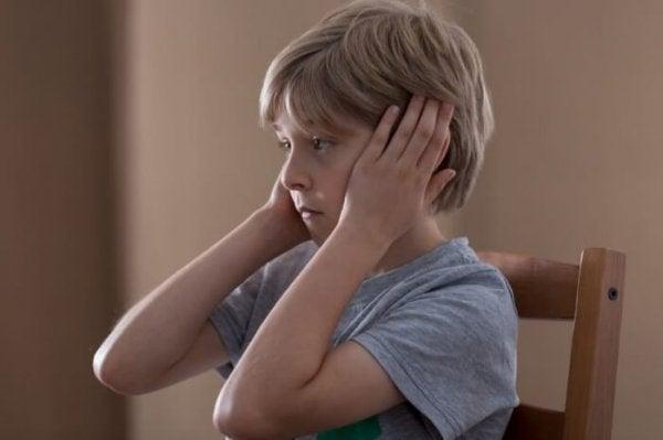 Dreng holder sig for ørerne