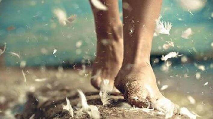 Bare fødder går med fjer flyvende omkring