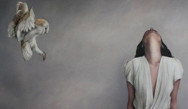 Kvinde foran grå væg med fugl tænker over sandheden om livet