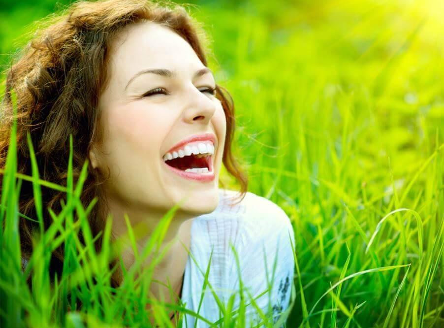Glad kvinde smiler på græsmark