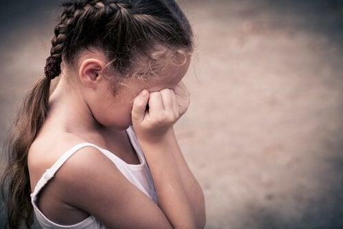 Barn græder og holder sig for øjnene på grund af barndomsdepression