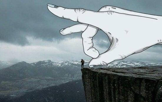 Hånd er ved at skubbe lille mand ned fra klippe
