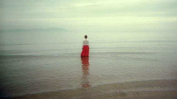 Kvinde med lang rød nederdel står ved hav