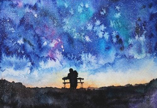 Par sidder på bænk og kigger på himmel