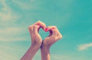 Kvinde danner hjerte med hænder, for selvkærlighed kan booste dit selvværd