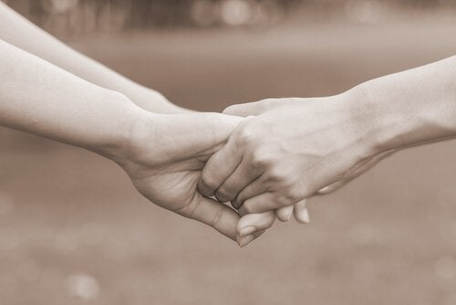 To personer holder i hånd som tegn på tilgivelse
