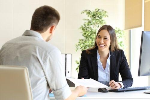 To personer taler og smiler sammen ved skrivebord