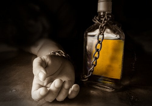 Hånd er lænket til flaske som symbol for alkoholisme