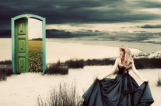 Kvinde på snelandsskab kigger mod dør, der åbner mod eng