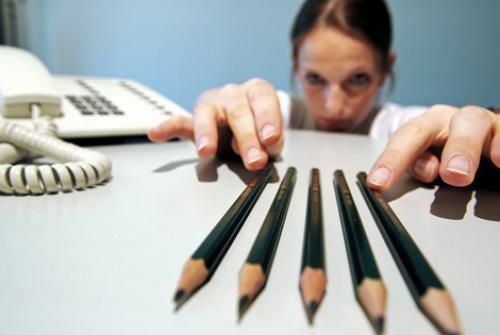 Kvinde lægger blyanter perfekt, da hun er fanget i et fængsel af perfektion