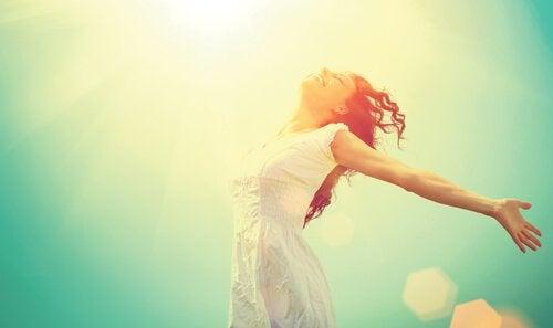 Kvinde i sollys og med åbne arme lever et liv fyldt med entusiasme
