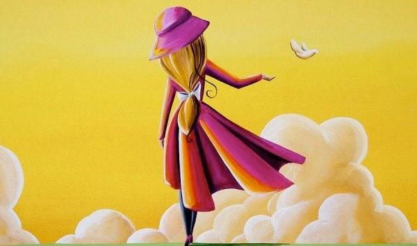 Kvinde på gul himmel med skyer rækker ud mod fugl