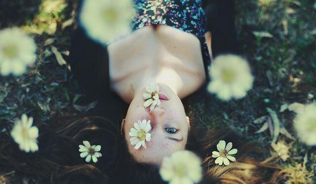 Kvinde ligger på jord med blomster over sig