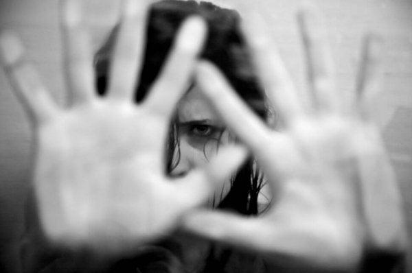 Kvinde med hænderne for ansigtet gemmer sig fra frygt