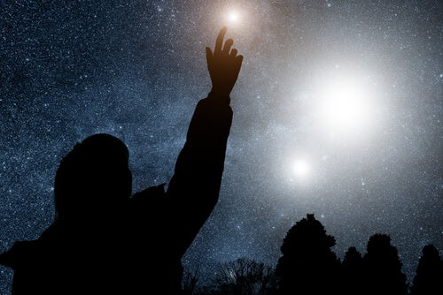 Mand rækker ud mod stjernerne