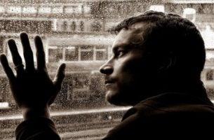 Mand ser længselsfuldt ud af vindue