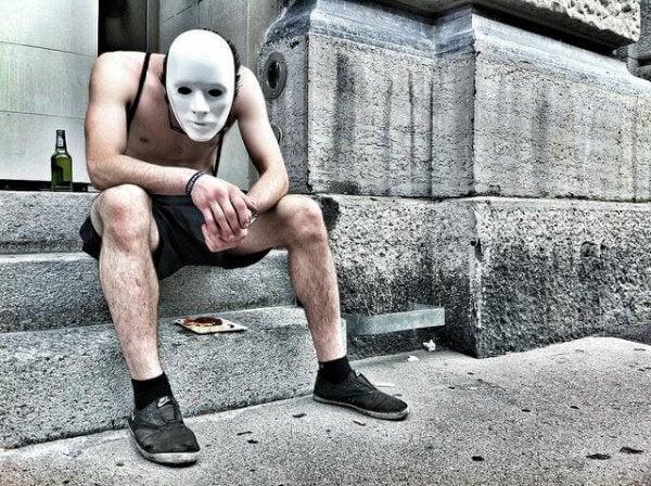 Mand bærer maske som en forklædning af alkoholisme