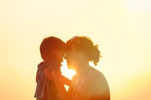 Mor og barn krammer foran sol