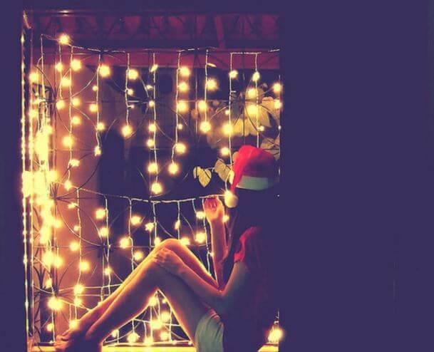 Pige i nissetøj sider foran lysranker og nyder julen