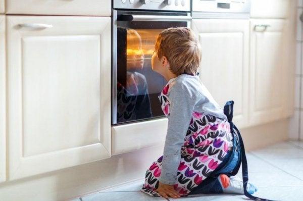 Dreng sidder foran tændt ovn