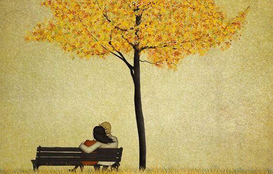 Par sidder tæt sammen på bænk under træ