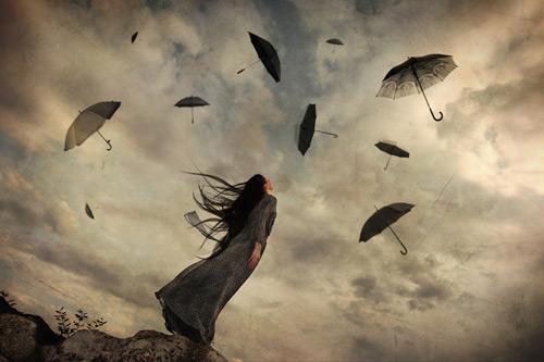 Kvinde kigger op på stormfuld himmel med flyvende paraplyer