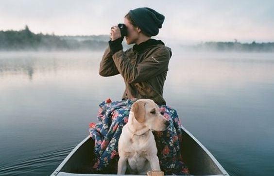 Person i båd med hund på sø