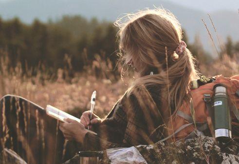 Kvinde sidder på mark og skriver og nyder lykke