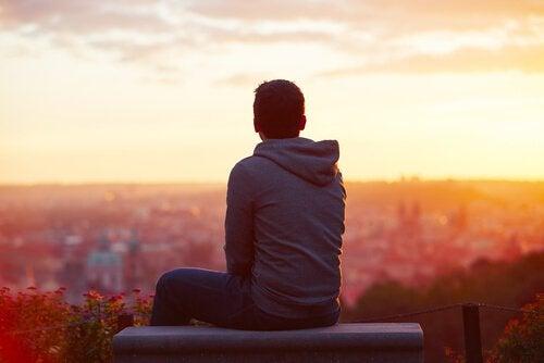 Mand kigger ud på solopgang over storby