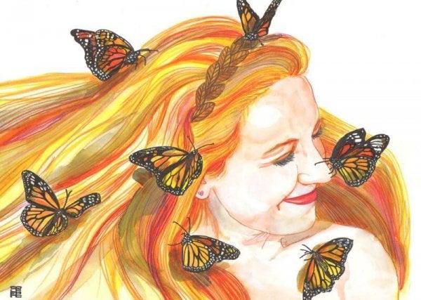 Kvinde med sommerfugle i håret og stort smil