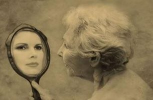 Ældre kvinde ser yngre ansigt i spejl på grund af demens
