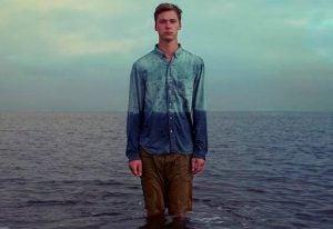 Mand foran hav på strand