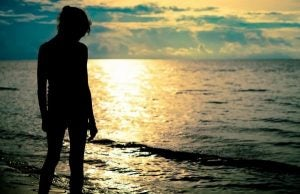 Kvinde på strand foran hav