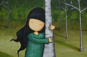 Pige klamrer sig til træ