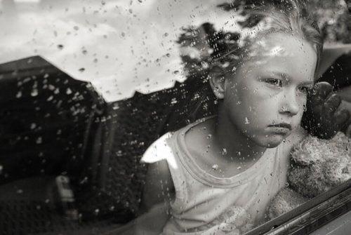 Trist barn kigger ud af vindue