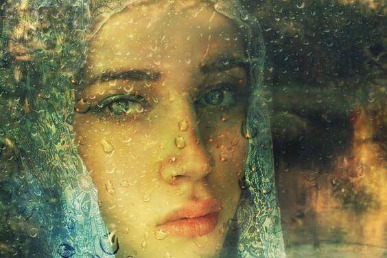 Kvinde kigger ud på regnen gennem vindue
