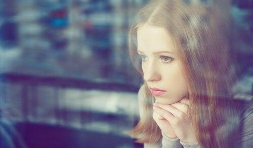 Trist kvinde kigger ud af vinduet