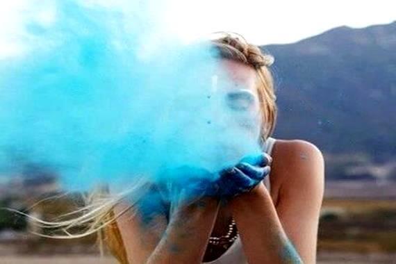 Pige puster blå røgsky