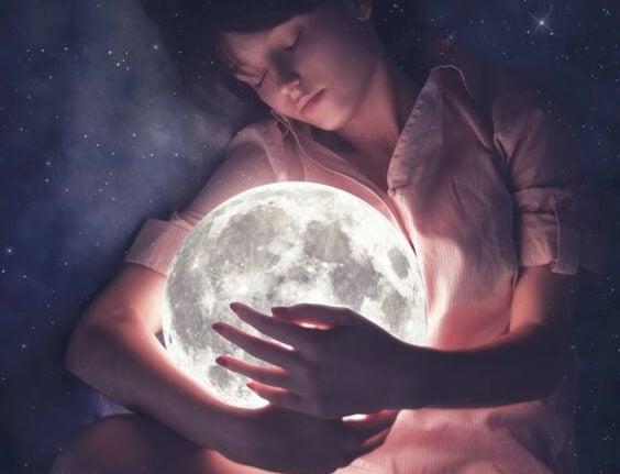 Barn sover med lysende måne i armene