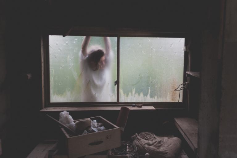 Person udenfor vindue er trist på grund af dysthymi