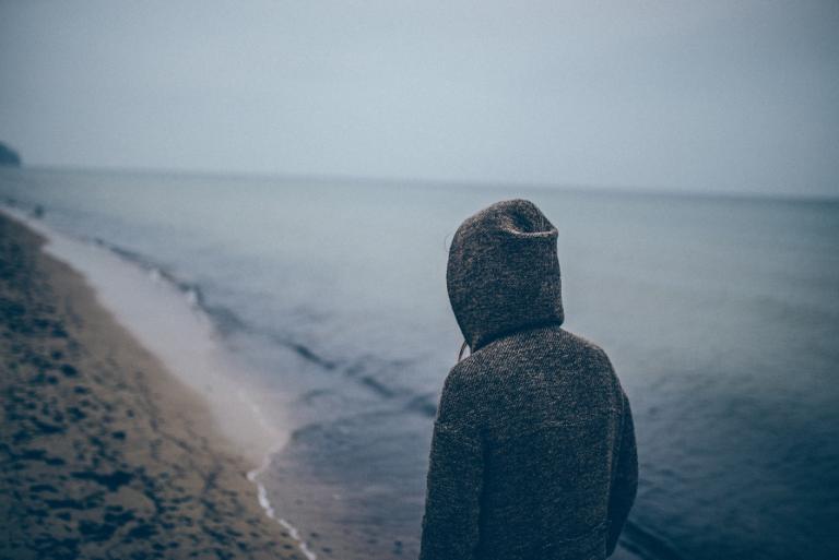 Deprimeret kvinde på strand er trist på grund af dysthymi
