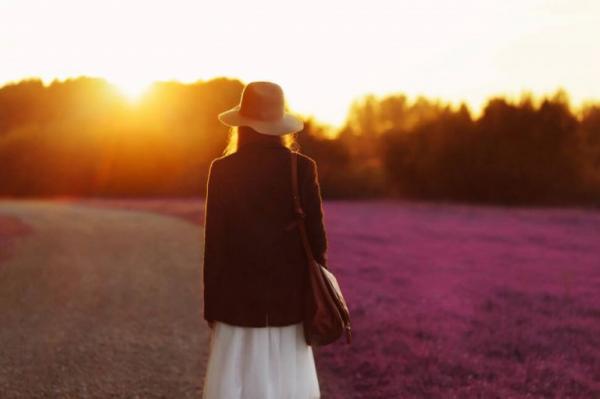 Kvinde med hat på blomstermark foran solnedgang