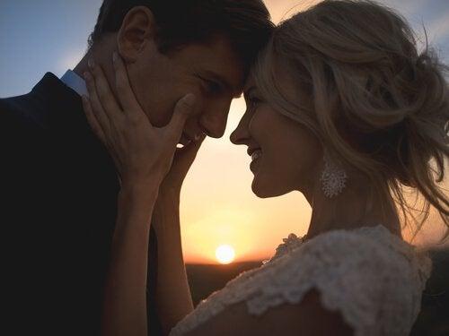 Nygift par nyder kærlighed foran solnedgang