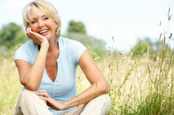 Smuk kvinde på halvtreds sidder på mark og smiler